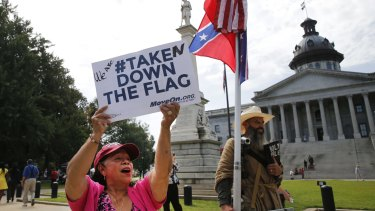 Maria Calef, of Columbia, South Carolina, waves a sign as she celebrates in front of the South Carolina statehouse.