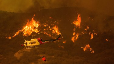 A helicopter carries water while trying to keep a wildfire from jumping Santa Ana Road, near Ventura, California on Saturday.