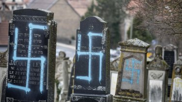 Vandalized tombs with tagged swastikas are pictured in the Jewish cemetery of Quatzenheim, in eastern France, on Tuesday, February 19, 2019.
