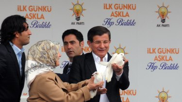 Turkish Prime Minister Ahmet Davutoglu and his wife Sare release doves at an AKP rally in Diyarbakir, a city with a large Kurdish population that in recent elections voted for the party in significant numbers.