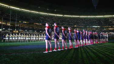 Players stand for the Last Post for the Anzac Day-eve clash in 2015.