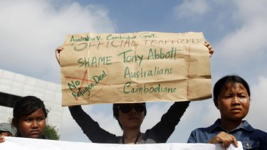 Protesters in Phnom Penh hold signs during a demonstration against Cambodia's plans to resettle intercepted refugees in September.