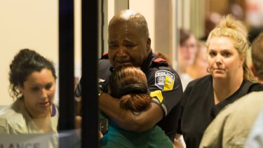 A Dallas Area Rapid Transit police officer receives comfort at the Baylor University Hospital emergency room entrance.
