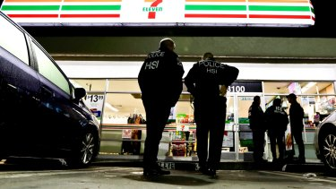 US Immigration and Customs Enforcement agents serve an employment audit notice at a 7-Eleven convenience store in Los Angeles.
