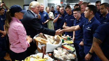 President Donald Trump, with first lady Melania Trump, greets and hands out sandwiches to US Coast Guard members.