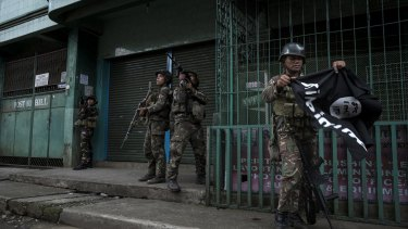A soldier carries an Islamic State flag seized while clearing a street of militants in Marawi city, southern Philippines.