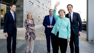 German Chancellor Angela Merkel waves as she arrives with Dutch Prime Minister Mark Rutte, right, for a visit to chip manufacturer ASML in Veldhoven, near Eindhoven, Netherlands last week.