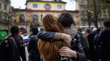Two girls embrace opposite the main entrance of Bataclan concert hall as French police lift the cordon following Fridays terrorist attacks.