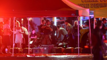 Medics treat the wounded as Las Vegas police respond to the shooting on the Las Vegas Strip on Sunday.
