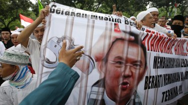 Muslim protesters hold a banner calling for the arrest of Jakarta Governor Basuki Tjahaja Purnama, popularly known as Ahok, outside City Hall in Jakarta.