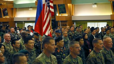 US and Philippine military officers stand at attention during the entrance of the colours at the opening ceremony of the annual joint US-Philippines military exercise.