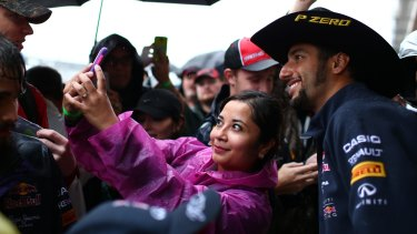 Daniel Ricciardo poses for photographs with fans in pit lane.