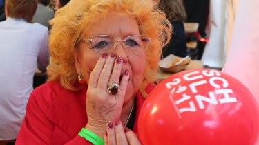 A woman at the election party of Germany''s Social Democrats reacts as she hears firsts results of the parliamentary elections in Berlin.