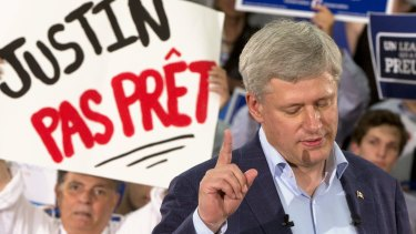 "Canadian Prime Minister Stephen Harper speaks to supporters during a rally in Montreal. The sign in the background reads: ""Justin (Trudeau) not ready""."