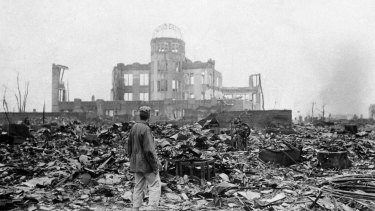 An Allied correspondent stands in the rubble of Hiroshima a month after the first atomic bomb was dropped by the US.