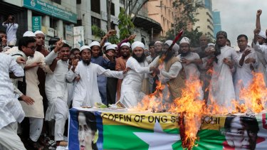 Bangladeshi activists from various Islamic groups burn a Myanmar flag and mock coffin during a protest in Bangladesh, against the persecution of Rohingya Muslims.