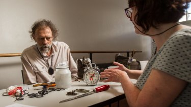 Taking their time: Karla Strambini, right, came from Montmorency, across town, to have the leg of her alarm clock fixed by John Harland, a volunteer at the Melbourne Repair Cafe.