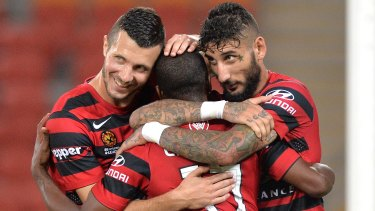 Happy days are here again: Western Sydney's Romeo Castelen celebrates with teammates after scoring against the Roar.
