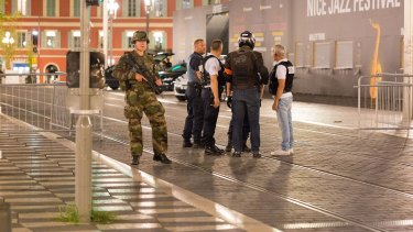 Police officers and a soldier stand by the sealed-off area where the attack took place.