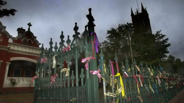 Ribbons tied to the fence at St Alipius Presbytery, church and old boys school in Ballarat pay tribute to the victims and survivors of child abuse.