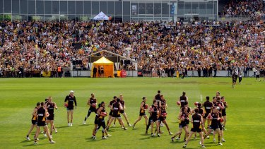 Supporters watch Hawthorn players at the final training day of 2012 Waverley.