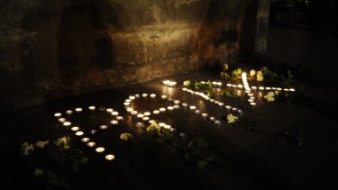 """Lit candles forming the word """"peace"""" in French are layed outside the Capitole building in Toulouse, southern France."""
