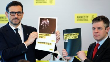 Amnesty International East Asia Director Nicholas Bequelin, left, and Deputy Director of Global Issues James Lynch hold the copies of reports.
