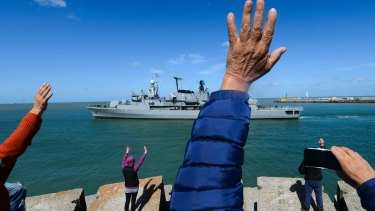 People wave to the Argentine destroyer Sarandi as it leaves a navy base in Mar del Plata, Argentina, to participate in the search of the missing submarine.