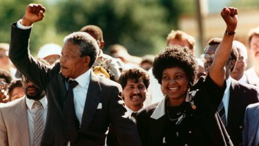 Nelson and Winne Mandela walk together, raising clenched fists, upon his release from Victor prison, Cape Town, after 27 years in detention in 1990.