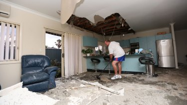 Frank Partlic cleans up rubble in his home.