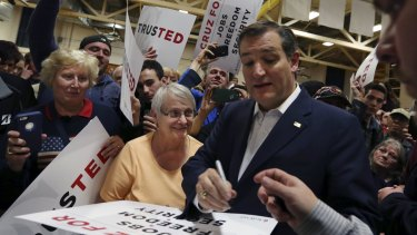 Ted Cruz signs posters for his supporters at a campaign rally on Friday.