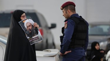 A Bahraini protester holds up a picture of Saudi Shiite cleric Sheikh Nimr Baqir al-Nimr confronting a riot police officer in Bahrain in January 2016. Qatar is out of step with its neighbours on the question of Iran, which has championed Shiite rights in Saudi Arabia, Yemen and Bahrain.