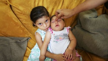 Seven-month-old Luhandra Vitoria, who was born with microcephaly, sits with her sister Jasminy in Recife, Brazil, where the first cases of Zika-related microcephaly were discovered last year.