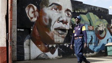 A security guard walks past a wall mural depicting US President Barack Obama  in  Nairobi.