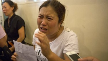Wang Baoxia talks to a journalist about her missing brother Wang Quan outside a government press conference in Tianjin on Saturday.