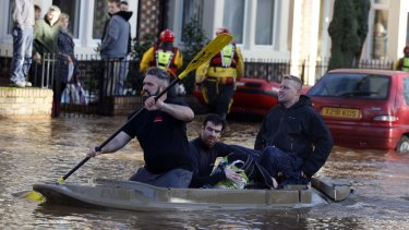 People are rescued from their homes in a kayak after floods on Warwick Street in Carlisle, England.