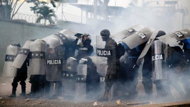 Police stand amid tear gas as they clash with supporters of opposition presidential candidate Salvador Nasralla near the institute where election ballots are stored in Tegucigalpa, Honduras.