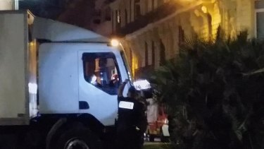 Police shine a light in the cab of a truck which ploughed into a crowd in Nice, killing 84.