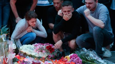 Mourners outside the shopping centre that was on Friday the scene of a devastating shooting that killed nine people.