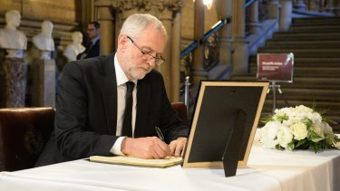 Opposition leader Jeremy Corbyn adds his name to a book of condolence at Manchester Town Hall.