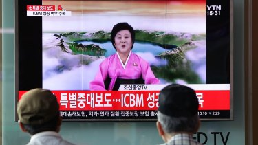 People watch North Korea's KRT television announcing the launch of an intercontinental ballistic missile.