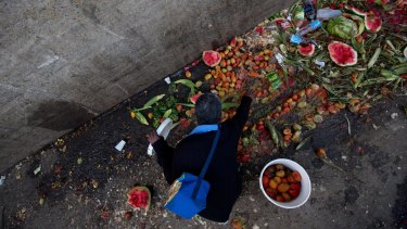 Pedro Hernandez goes through discarded tomatoes from the trash area of the Coche public market in Caracas, Venezuela.
