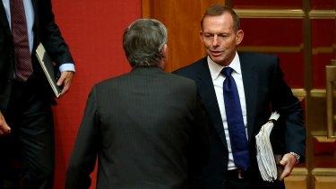Former prime minister Tony Abbott congratulates Senator Bill Heffernan after the Senator delivered his valedictory speech earlier on Wednesday.