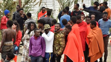 Migrants stand together after storming a fence to enter the Ceuta on December 9.