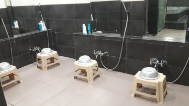 Though far from home, Japanese workers like to bathe in traditional style sitting on stools in a row and pouring water from basins over themselves.