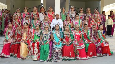 Mahesh Savani with brides during a wedding event in 2014.