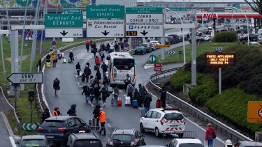 Travellers walk on the highway to the Orly airport, south of Paris, which was evacuated after a man was fatally shot there.