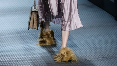 A model wears footwear with wisps of fur as part of the Gucci women's Fall-Winter 2015-2016 collection in Milan, Italy.