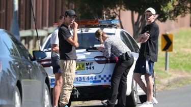 Police detectives talk to teenagers close to a house after a 15-year-old boy was shot in the head at a home in Glenfield.