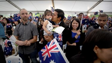 Michael Bulanan giving his two-year-old daughter a kiss while his wife Rachelle Bulanan watches on at the Australia Day ceremony in Sunshine.